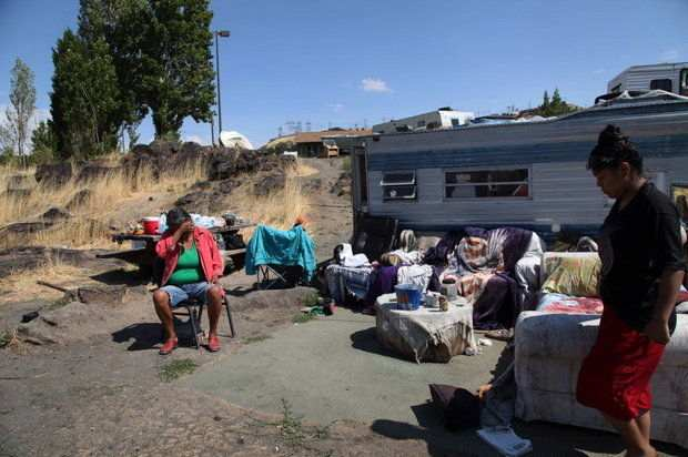 In this Aug. 22 photo at Lone Pine, resident Ranetta Spino, left, sits in front of the trailer home she shares with her relatives at the Native American fishing site on the Columbia River near The Dalles, (AP Photo/Gosia Wozniacka)